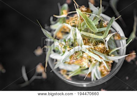 Dried linden flowers and leaves In a transparent glass bowl on Black Background.