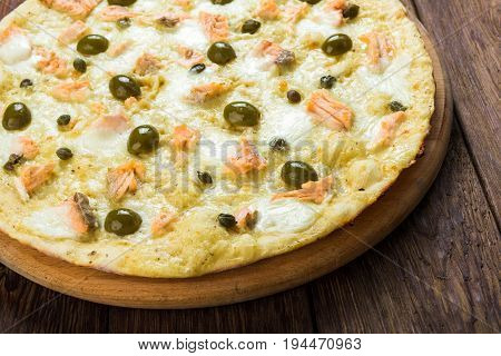 Seafood pizza with salmon on wood, thin pastry crust with slice cut, fast food delivery