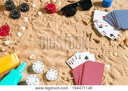 Beachpoker. Chips and cards on the sand. Around the seashells, sunglasses and suntan cream. Top view. Copy space. Flat lay