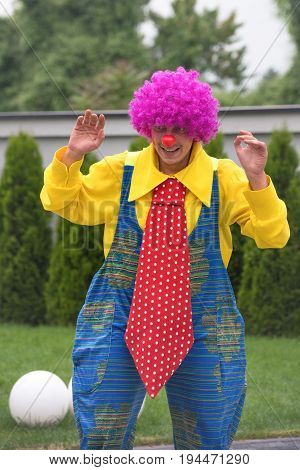 Happy clown with big red tie performing his show