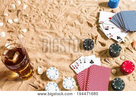 Beachpoker. Chips and cards on the sand. Around the seashells and cold drink in a glass. Top view. Copy space. Flat lay