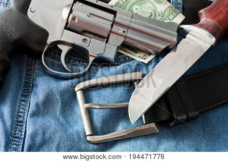 Chromed revolver jeans and a hunting knife close-up