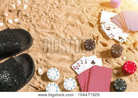 Beachpoker. Chips and cards on the sand. Around the seashells and flip flops. Top view. Copy space. Flat lay. Sun flare
