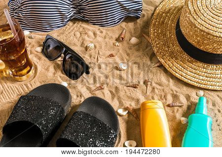 Summer bikini and accessories stylish beach set, Beach bikini summer outfit and sea sand as background, Top View, Concept. Copy space