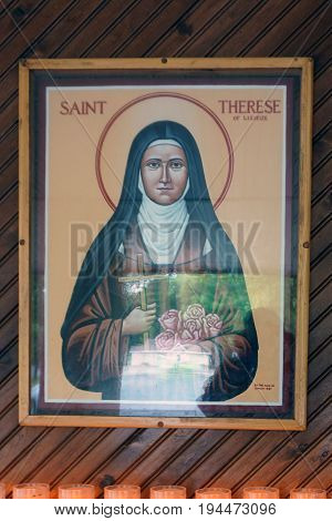 INDIAN RIVER, MICHIGAN / UNITED STATES - JUNE 18, 2017: Visitors and devotees may offer donations and light candles below a portrait of Saint Therese of Lisieux, at the Cross in the Woods Roman Catholic National Shrine.