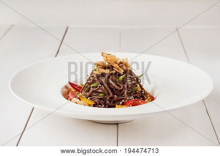 Soba noodles of buckwheat Noodles of buckwheat yellow pepper, tomato and herbs. Pan-Asian cuisine. Place for text. Square photo size. Copy space