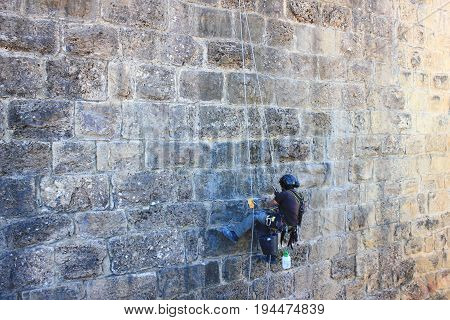 Construction worker making repairs on historic old brick wall. Industrial, rebuilding, renovation crew member, work concept