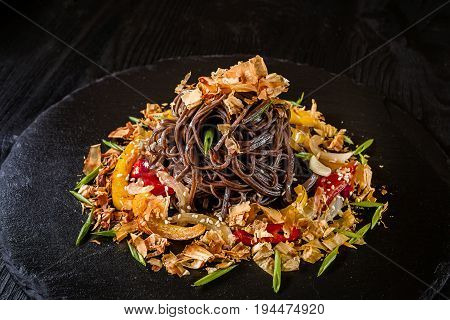 soba noodles of buckwheat Noodles of buckwheat yellow and red pepper, herbs. Pan-Asian cuisine. On stone tray on dark wooden table. Place for text.