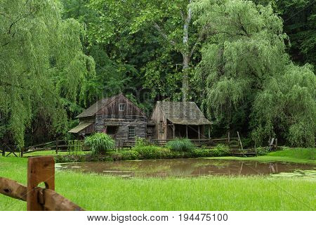Wide shot of Cuttalossa Farm Water Wheel, Sheep Barn, Clapboard Cottage, and Pond with Wooden Fence in Foreground