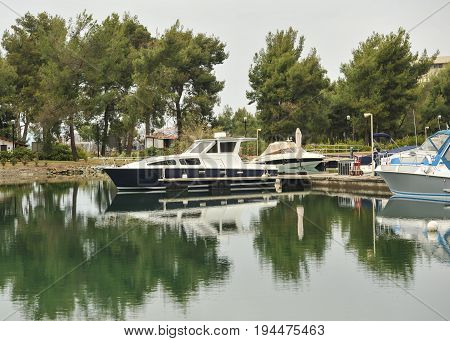Yachts anchored at the marina.Sailboat harbor, many moored sail yachts in the sea port, modern water transport,summertime vacation, luxury lifestyle and wealth concept.Modern yachts in harbor