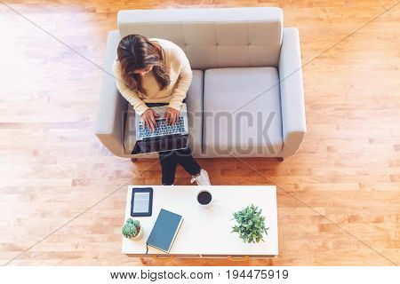 Happy young latina woman working on her laptop at home