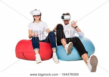 Excited young couple experiencing virtual reality seated on beanbags isolated on white background. A young couple, both in jeans, white sneakers and T-shirts. A family