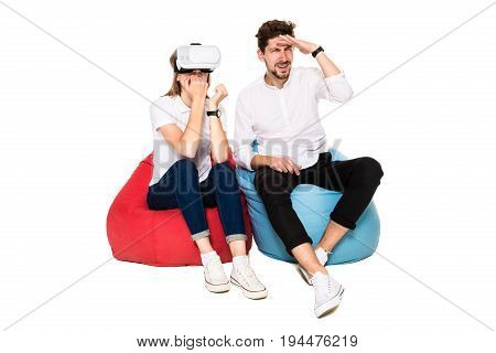 Smiling friends experiencing virtual reality glasses seated on beanbags isolated on white background. Experiencing virtual gaming adventure.