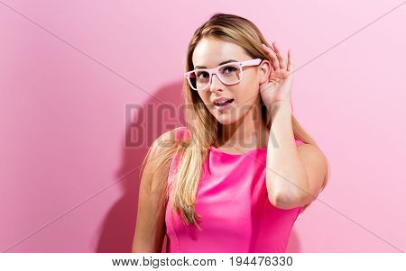 Young woman listening on a pink background