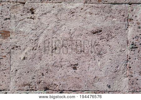 Abstract background: rough natural pink tuff building stone close-up