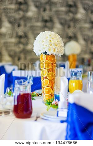 Table set for wedding banquet with cutlery. Salads appetizers and glasses with wine. Decoration elements - vases with orange slices and white chrysanthemum flowers.