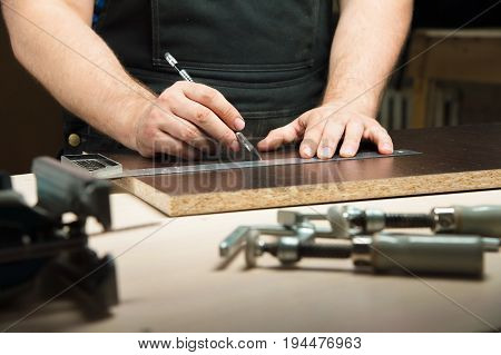 Men's hands draw a pencil on the ruler with a sub-standard template for cutting out furniture details next to the jigsaw and furniture clips.