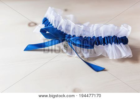 Bride's garter. Bride's traditional symbolic accessory. White laces with blue bow. Close up.
