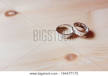 Pair of golden wedding rings with geometrical ornament on wooden background. Symbol of love marriage and the fifth (