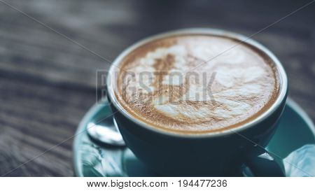 A cup of hot latte coffee with latte art in blue coffee cup on vintage wooden table