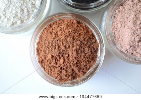 Red cosmetic clay for facial masks with pink clay kaolin and activated charcoal closeup top view