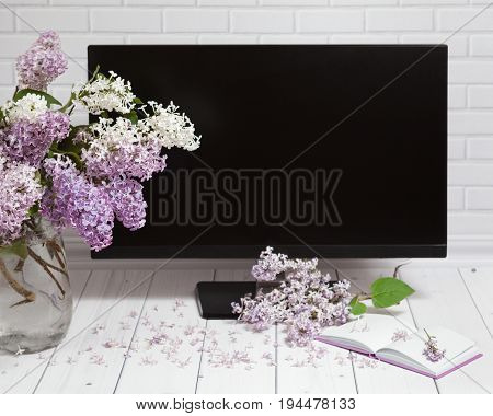 Beautiful white and violet lilac flowers bouquet in vase with opened note-book and black monitor screen on the white brick and wooden background, mock up perspective front view