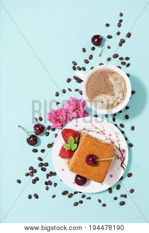 Tasty piece of cake on the white plate and cup of coffee, decorated with flowers, coffee beans, strawberries and cherry on the light mint background with empty place, top flat view, diagonal composition