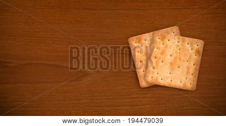 Fresh baked cream crackers in two pieces isolated on dark teak wood background with copy space for text decoration