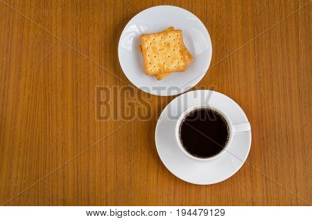 Black coffee in white ceramic cup on saucer over dark teak wood background served with cream crackers on white plate with copy space for text insertion top view (flat lay)