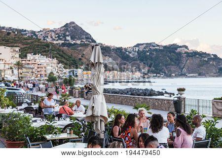 People In Sidewalk Restaurant In Giardini Naxos