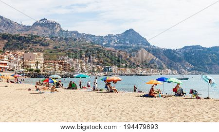 Tourists On Sand Beach In Giardini Naxos Town