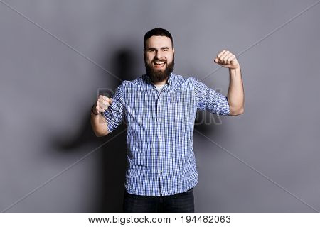 Excited bearded man very glad to success. Young cheerful guy smiling at camera and gesturing with hands, gray studio background
