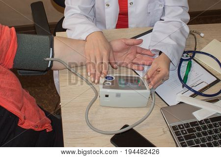 Female medicine doctor measuring blood pressure to patient while chatting her. Woman communicate with physician during medical examination. Medical insurance concept