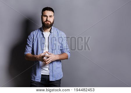 Bearded man with public speaker gesture. Fingers connected at fingertips, pose which imposes power and patience, gray studio background, copy space