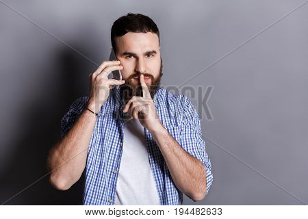 Bearded man talking on phone point be quiet. Young guy having important conversation, showing hush sign with finger on lips, gray studio background, copy space