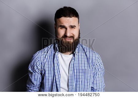 Feeling upset. Portrait of sad bearded man, looking at camera. Young unhappy guy grimacing, gray studio background