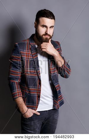 Puzzled young man stroking beard looking at camera. Serious bearded hipster touching his face, gray studio background