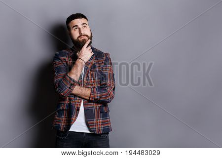 Pensive young bearded hipster looking upwards. Handsome relaxed guy in checkered jacket dreaming about something, lost in thoughts, gray studio background, copy space