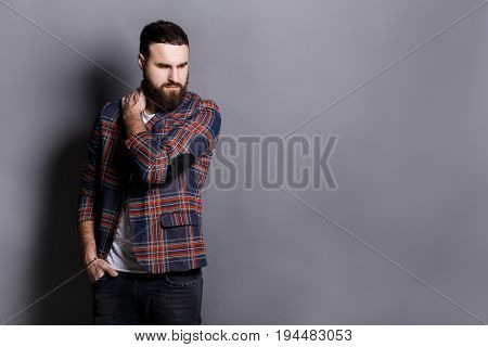 Unhappy man suffering from neck or shoulder pain. Young bearded hipster holding his neck with sad expression, gray studio background, copy space