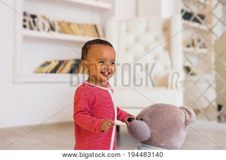 Happy baby boy playing with his teddy bear.