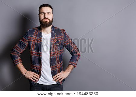 Serious trendy bearded man posing with hands on hips. Young hipster standing in irritated pose, gray studio background, copy space