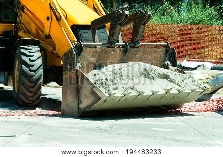 Wheel loader bulldozer excavator construction machinery front side carries sand. Construction site machinery.