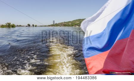 Photographing from the stern of the ship. Summer river landscape. The Volga river in Saratov, Russia. Russian flag, the tricolor. Road bridge between the cities of Saratov and Engels