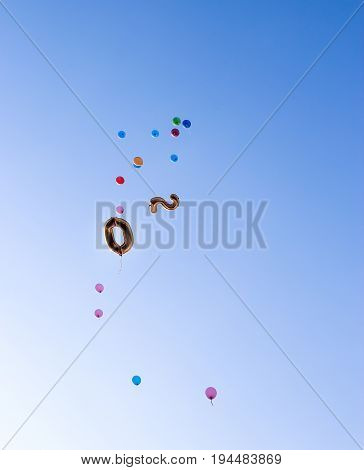 Balloons in the form of number 20 and colorful fly high into the blue clear sky. Copy space