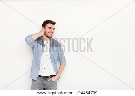 Handsome man touching his hair. Young confident guy in relaxed pose, isolated on white background. Flirt, seduction concept