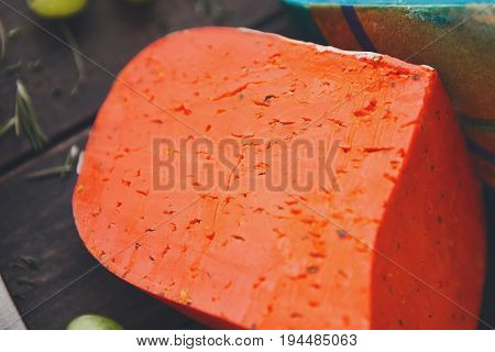 Gouda pesto red cheese closeup. Red and blue cheese on rustic wood background