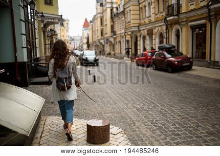 View on a city street with woman walking on a sidewalk. Travelgirl taking a walk in european city.