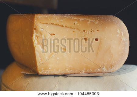 Parmesan cheese as wheel and piece closeup. Aged cheese at grocery shop background