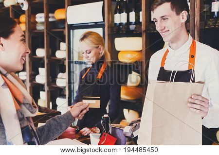 Retail, credit card payment service. Customer paying for order of cheese in grocery shop.
