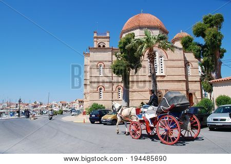AEGINA, GREECE - APRIL 26, 2017: A horse and carriage giving tourists rides passes the Panagitsa church on the harbour front at Aegina Town on the Greek island of Aegina.